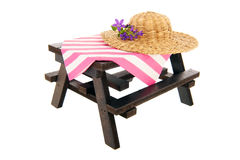 Picnic table with straw summer hat Stock Photo