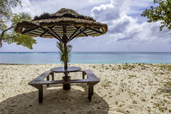 Picnic Table with Straw Umbrella on Tropical Beach Stock Images