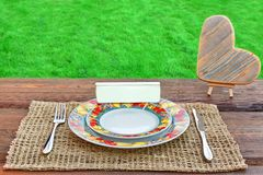 Picnic Table With Tableware, Wooden Heart And White Blank Signbo Stock Photos