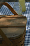 Picnic table with vintage picnic basket, blue checked table cloth. Bottles of lemonade and drinking jar glasses Stock Image