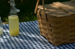 Picnic table with vintage picnic basket, blue checked table cloth. Bottles of lemonade and drinking jar glasses Stock Images