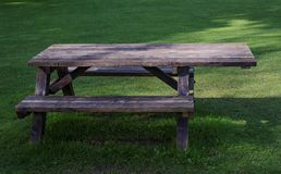 Picnic table for wheelchair users. A wooden picnic table with integrated seating. The table has an extended top which allows it to be used by a person in a Royalty Free Stock Photography
