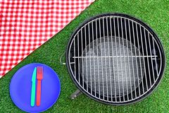 Picnic Tablecloth, Plate, Fork, Knife, BBQ Grill  On The Lawn Stock Photography