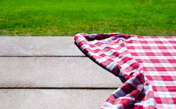 Picnic tablecloth on the table. Picnic tablecloth textile on the table with grass background Stock Image