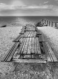 Picnic tables with benches on Whitstable beach in monochrome. A row of wooden picnic bench tables on Whitstable beach, Kent, Uk, with wooden groynes and a view Royalty Free Stock Photos