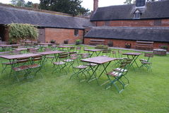 Picnic tables and chairs on a lawn Royalty Free Stock Photo