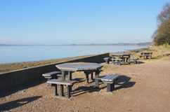 Picnic tables by edge of Estuary Stock Photo