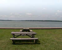 Picnic tables near water. Dining space at river's edge with two wooden picnic tables in grassy park setting Royalty Free Stock Images