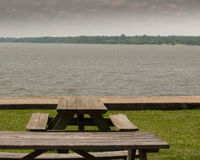 Picnic tables at edge of river Stock Photos