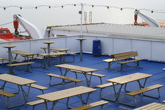 Picnic Tables on Ship's Deck. Wooden picnic tables and benches on the deck of a cruise ship Royalty Free Stock Photography