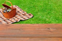Picnic  Tabletop Close-up. Picnic Basket and Blanket On The Lawn. Empty Wooden Picnic Tabletop Close-up. Picnic Basket and Blanket On The Summer Lawn In The Royalty Free Stock Image