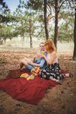 Picnic time. Love and tenderness, dating, romance, lifestyle concept. Picnic - Young couple in spring meadow. Stock Photo