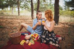 Picnic time. Love and tenderness, dating, romance, lifestyle concept. Picnic - Young couple in spring meadow. Picnic. Beautiful smiling couple enjoying picnic royalty free stock photography