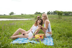 Picnic. Two girls lay in a grass on picnic Royalty Free Stock Photos