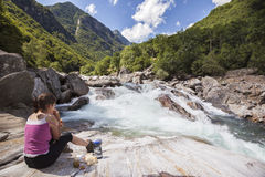Picnic at valley riverside. Woman having picnic on beautiful mountain riverside in Switzerland, Verzasca Valley Stock Image