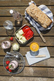 Picnic with wholemeal-wheat-spelt-bread, dips, crudites, strawberry-yogurt and lemonade. On wood table Stock Image