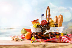 Picnic wicker basket with food on table on the beach. Picnic wicker basket with food on wood table on the beach with blue sky background and sun. Picnic concept Stock Photography