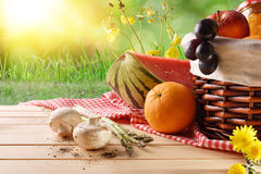 Picnic wicker basket with food on table in field closeup. Picnic wicker basket with food on table in the field with green nature background. Picnic concept close Royalty Free Stock Photography