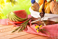 Picnic wicker basket with food on table in field elevated. Picnic wicker basket with food on table in the field with green nature background. Picnic concept Royalty Free Stock Photography