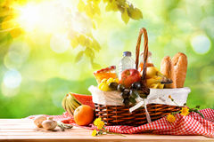 Picnic wicker basket with food on table in the field