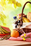 Picnic wicker basket with food on table in field vertical. Picnic wicker basket with food on table in the field with green nature background. Picnic concept Stock Photo