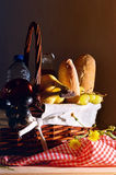 Picnic wicker basket with food on wood table dark. Picnic wicker basket with food on wood table. Picnic dark composition. Front view. Vertical composition Stock Photo