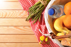 Picnic wicker basket with food on wood table top. Picnic wicker basket with food on wood table. Picnic concept close up. Top view. Horizontal composition Stock Photography