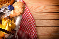 Picnic wicker basket with food on wood table top view. Picnic wicker basket with food on wood table. Picnic concept close up. Top view. Horizontal composition stock images
