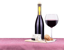 Picnic with wine and food. Picnic lunch on a red and white gingham tablecloth including a wine,bread,cheese and grapes Stock Images