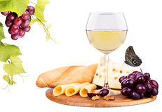 Picnic with wine and food. Picnic lunch on a wooden board including a wine,bread,cheese and grapes Stock Images