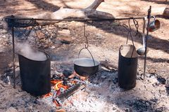 Picnic in the woods on an open fire. Cooking on the fire diluted in the woods on a camping pot, boiling water, an open flame on charcoal. Smoked walls of dishes stock image