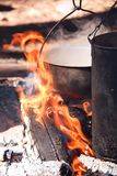Picnic in the woods on an open fire. Cooking on the fire diluted in the woods on a camping pot, boiling water, an open flame on charcoal. Smoked walls of dishes stock images