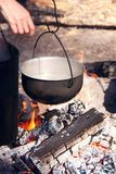 Picnic in the woods on an open fire. Cooking on the fire diluted in the woods on a camping pot, boiling water, an open flame on charcoal. Smoked walls of dishes stock photos
