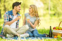 Picnic. Young beautiful couple dressed casual having picnic in park and drinking wine Royalty Free Stock Images