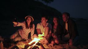 Picnic of young people with bonfire on the beach in the evening. Cheerful friends taking pictures on the phone stock video