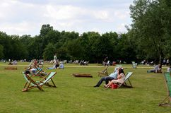 Picnickers relax on deckchairs and grass Hyde Park London England. London, England - June 20, 2014: Picnickers in London enjoy a sunny day by relaxing at London' Royalty Free Stock Image