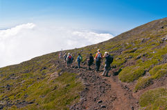 Pico. The group of tourists goes down from top of a volcano Stock Photo