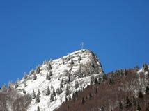 Pico coberto de neve da montanha a mais alta com uma cruz na parte superior Fotos de Stock Royalty Free