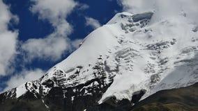 Pico coronado de nieve y cielo azul con las nubes en las montañas Tíbet de Himalaya metrajes