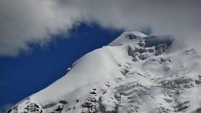 Pico coronado de nieve y cielo azul con las nubes en las montañas Tíbet de Himalaya almacen de video
