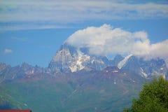 Pico da montagem Ushba coberto nas nuvens em montanhas de Cáucaso, região superior de Svaneti, Geórgia foto de stock