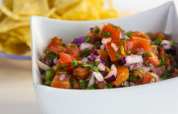 Pico de gallo. I a white bowl with tortillas chips royalty free stock photos