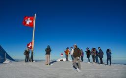 Pico de Jungfrau de la visita de los turistas con la bandera suiza foto de archivo