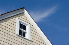 Pico de la casa con la ventana y el cielo azul Foto de archivo