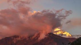Pico de la nieve de la montaña de Annapurna en la puesta del sol entre las nubes de mudanza en el Himalaya en Nepal Timelapse almacen de metraje de vídeo