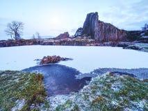 Pico de los pilares del basalto cubiertos por la nieve, piscina congelada Luna Llena en cielo azul en el fondo Imágenes de archivo libres de regalías