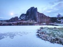 Pico de los pilares del basalto cubiertos por la nieve, piscina congelada Luna Llena en cielo azul en el fondo Fotografía de archivo libre de regalías