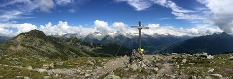 Pico de montaña con la cruz en las montañas europeas imagenes de archivo