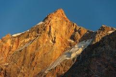 Pico de montaña del escarlata de la altura en rayos de la puesta del sol Imagenes de archivo