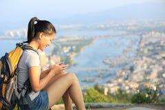 Pico de montaña del smartphone del uso del caminante de la mujer Fotografía de archivo